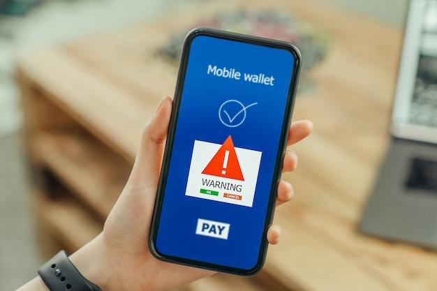 Mãos de mulher usando telefone e logon mobile banking on-line com mostram uma tela de aviso de perigos de malware.