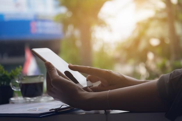 Mãos de mulher usando telefone inteligente para wprk na loja de café