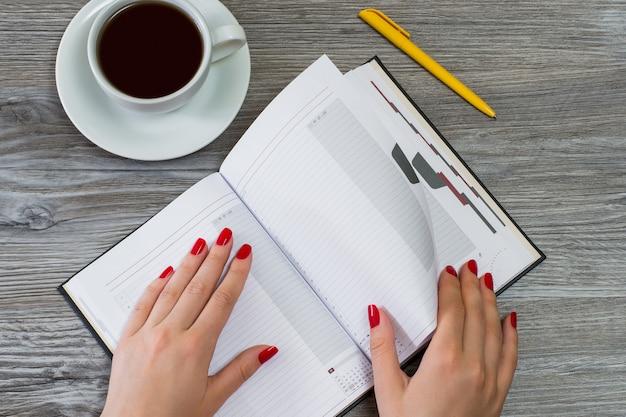 Mãos de mulher virando uma página em um caderno. uma xícara de chá e uma caneta estão no fundo. vista superior da foto