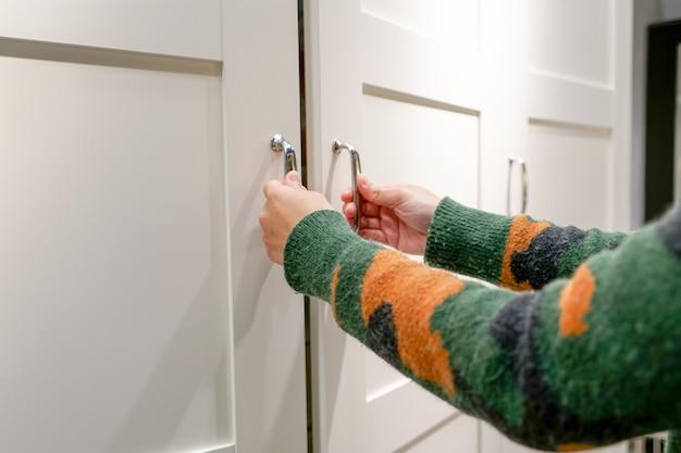 Mãos de mulheres abrem a porta do armário do armário