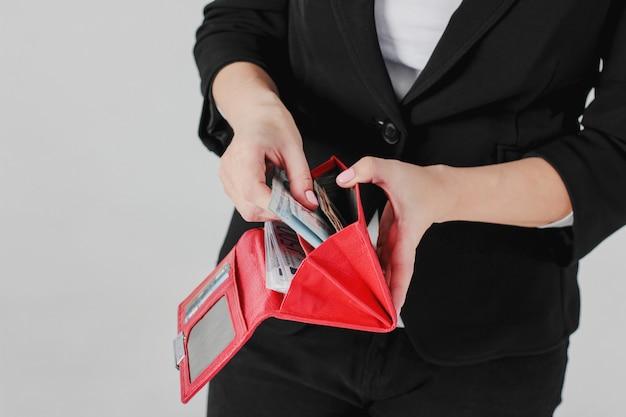 Mãos de mulheres aceitam dinheiro da bolsa vermelha em fundo cinza isolar