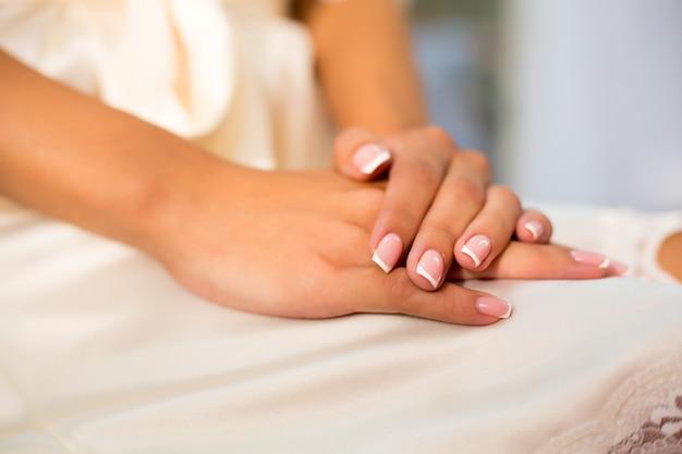 Mãos de mulheres bonitas com manicure francesa