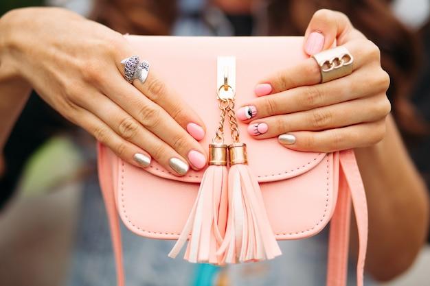 Mãos de mulheres bonitas com manicure na moda, segurando a adorável bolsa de pêssego.