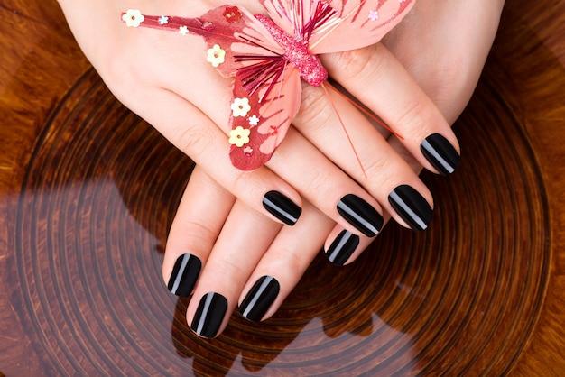 Mãos de mulheres bonitas com manicure preta após procedimentos de spa - conceito de tratamento de spa
