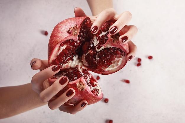 Mãos de mulheres bonitas com manicure vermelho escuro, fundo branco, segurando uma romã madura. extensão de unha. manicure, salão de spa. criativo, publicidade.
