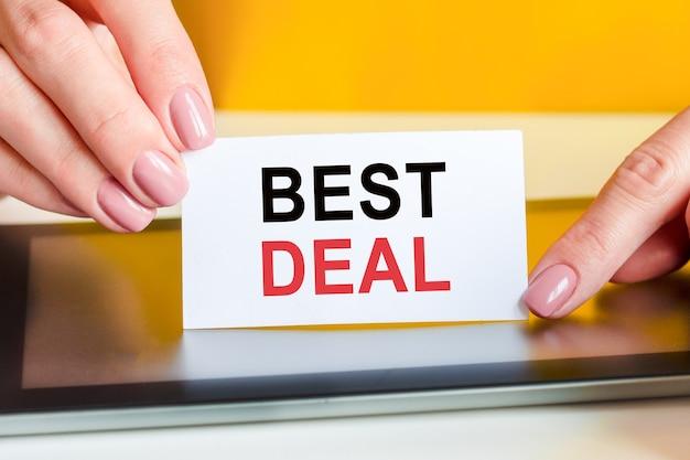 Mãos de mulheres bonitas segura um pedaço de papel branco com o texto: melhor negócio. fundo amarelo, superfície da tela do tablet, vista frontal, close-up. negócios, marketing, educação, conceito financeiro