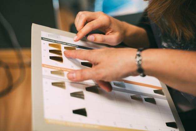 Mãos de mulheres com um catálogo de cores de tinta