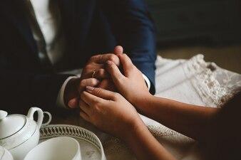 Mãos de mulheres e homens com anéis de casamento