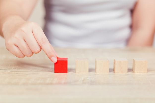 Mãos de mulheres, empilhando blocos de madeira em etapas.