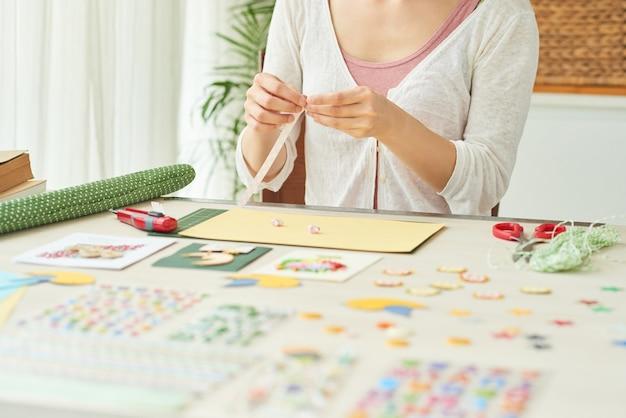 Mãos de mulheres fazendo estrelas com listras de papel colorido ao criar cartões comemorativos em casa