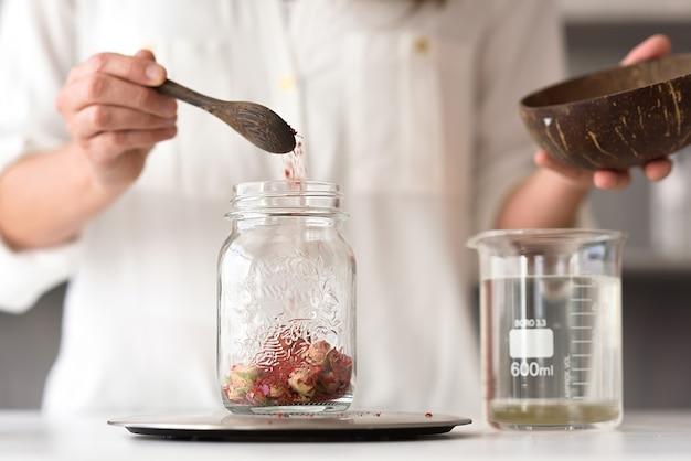 Mãos de mulheres jogando flores secas em um vaso e fazendo cosméticos orgânicos