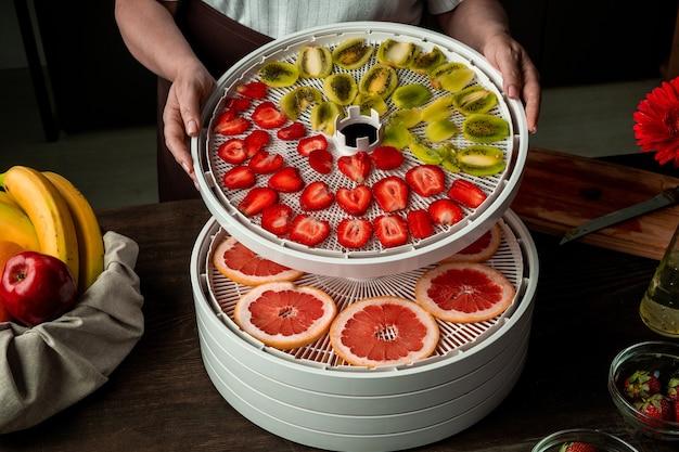 Mãos de mulheres maduras de avental pegando fatias secas de caqui ou outras frutas da bandeja superior da secadora de alimentos na cozinha