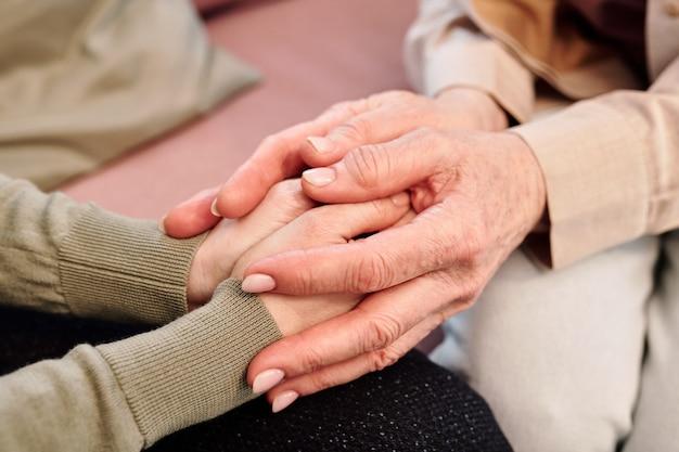 Mãos de mulheres maduras e jovens durante o apoio