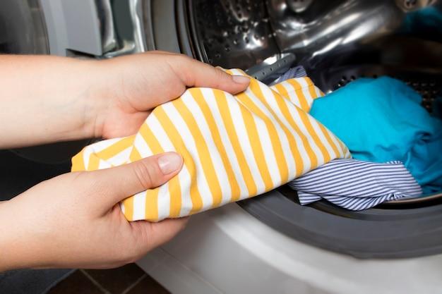 Mãos de mulheres puxam lençóis limpos do tambor da máquina de lavar roupa em casa e lavanderia