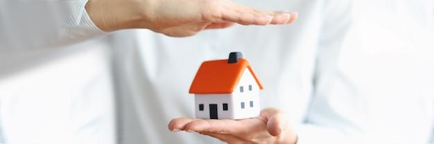 Mãos de mulheres salvam casa com conceito de telhado