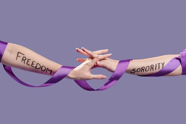 Mãos de mulheres se abraçando como sinal de irmandade