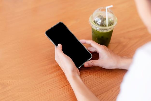 Mãos de mulheres segurando um smartphone de tela vazia em branco no café.