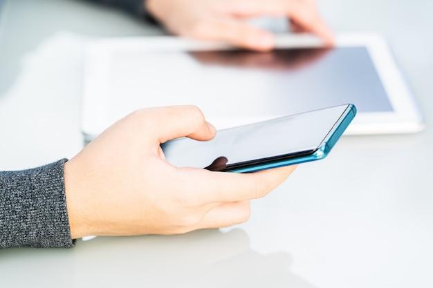Mãos de mulheres segurando um telefone com tela acima