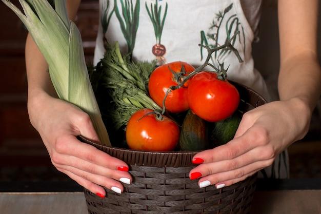 Mãos de mulheres segurando uma cesta de legumes