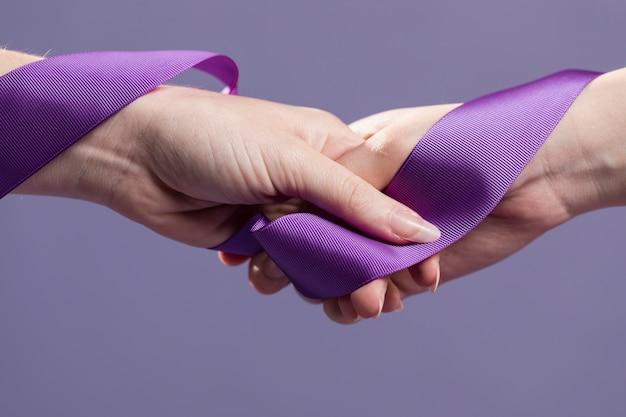 Mãos de mulheres segurando uma fita de cetim roxa