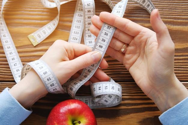 Mãos de mulheres segurando uma fita métrica. maçã vermelha para baixo. fechar-se. o conceito de dieta, estilo de vida saudável e nutrição adequada.