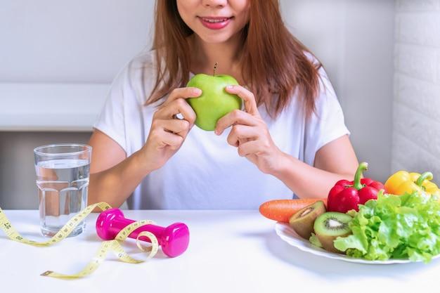 Mãos de mulheres segurando uma maçã verde com frutas, legumes, água, halteres e fita métrica