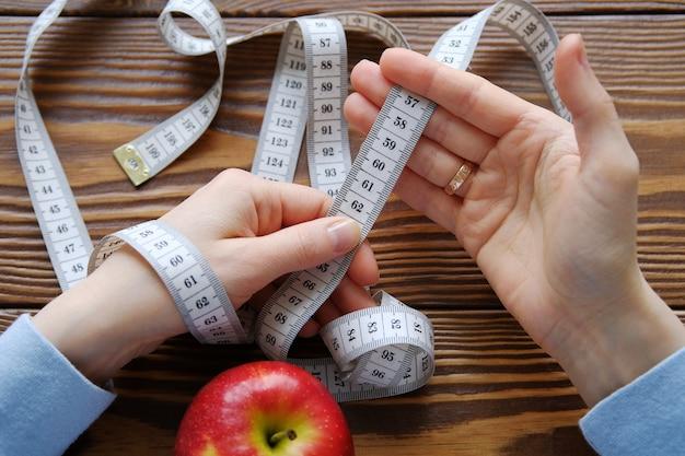 Mãos de mulheres segurando uma roleta, ao lado de uma maçã. o conceito de dieta, nutrição saudável.