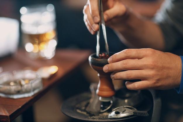 Mãos de narguilé shisha colocando tabaco para fumar e lazer