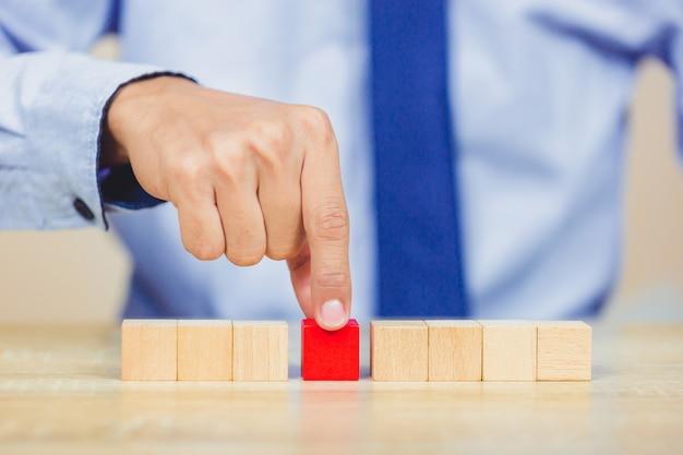 Mãos de negócios, empilhando blocos de madeira.