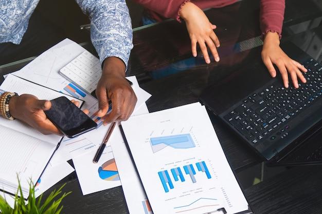 Mãos de negros segurando o telefone móvel no fundo de documentos financeiros no espaço de negócios