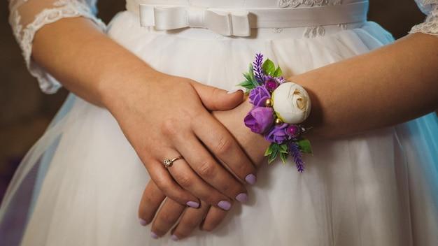 Mãos de noiva com flor de lapela decorativa em close-up de vestido de noiva