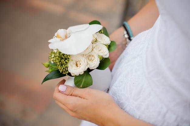 Mãos de noiva com um pequeno buquê de casamento