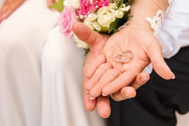 Mãos de noiva e noivo com anéis de casamento