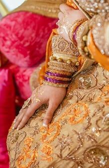 Mãos de noiva indiana paquistanesa decoradas com hena, joias, pulseiras e anéis na festa mehndi