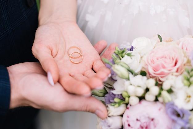 Mãos de noivos com alianças e um buquê de casamento