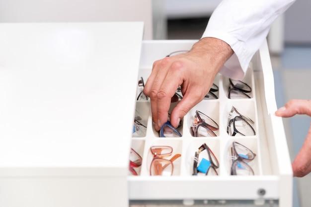 Mãos de oftalmologista close-up, escolhendo óculos de uma gaveta na loja óptica