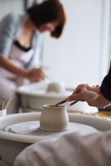 Mãos de oleira cortando o excesso de argila do pote que ela fez com uma ferramenta de arame