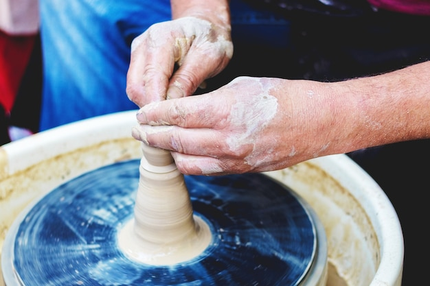 Mãos de oleiro habilmente formam um jarro em uma roda de oleiro