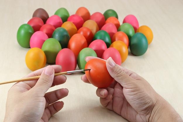 Mãos de ovos coloridos de pintura cristã contra o pincel, preparando-se para a páscoa