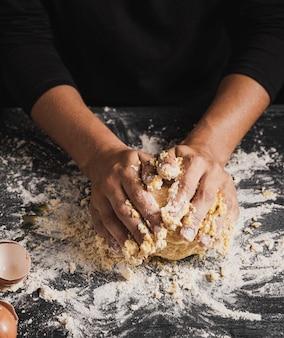Mãos de padeiro de alto ângulo misturando massa