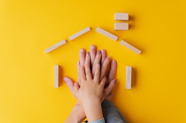 Mãos de pai, mãe e filho, uma em cima da outra, colocada em forma de casa, feita de estacas de madeira
