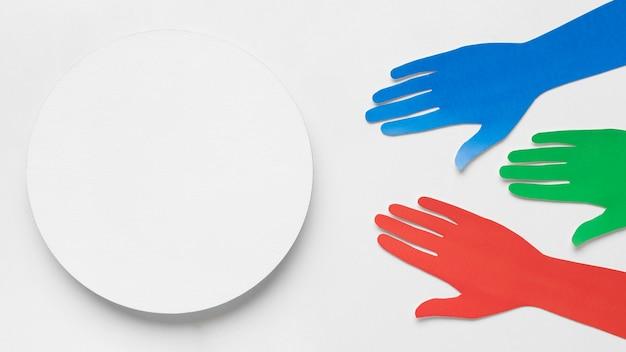 Mãos de papel de cores diferentes ao lado de um círculo branco