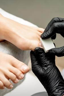 Mãos de pedicure polindo a unha de uma mulher com um lustrador de unha branca em um salão de beleza