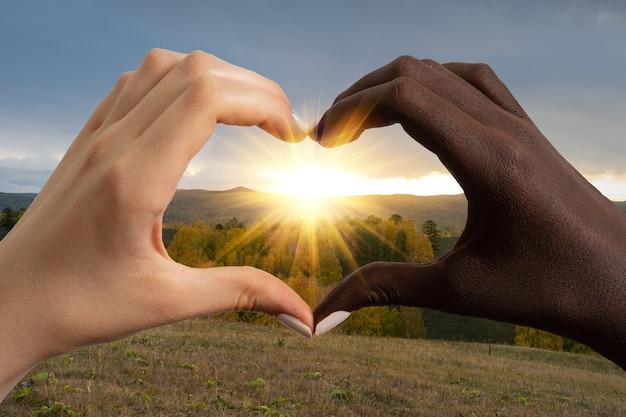 Mãos de pele negra e caucasianas em forma de coração em um fundo de pôr do sol sobre as montanhas Foto Premium