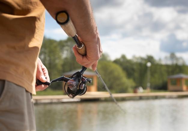 Mãos de pescador segurando a vara do carretel, isca de colher e pesca no lago, close-up.