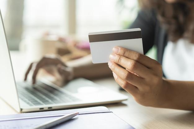 Mãos de pessoa às compras no ecommerce e usando cartão de crédito.