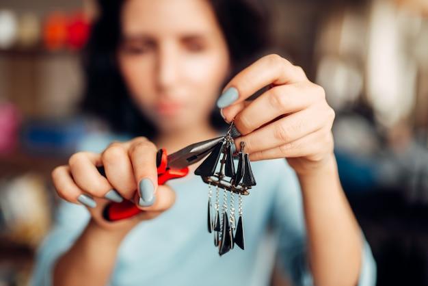 Mãos de pessoa do sexo feminino com um alicate, mestre em fazer brincos artesanais. trabalho de agulha, confecção de bijuteria