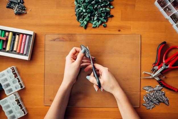 Mãos de pessoa do sexo feminino com uma tesoura, vista superior. joias artesanais. trabalho de agulha, confecção de bijuteria