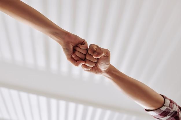 Mãos de pessoas batendo os punhos, visão de baixo, conceito de trabalho em equipe e cooperação