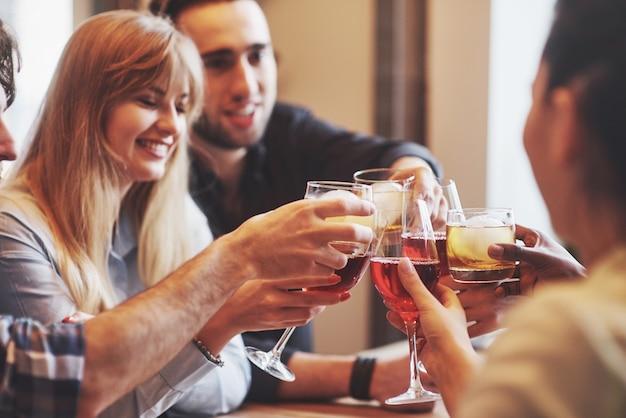 Mãos de pessoas com copos de uísque ou vinho, comemorando e brindando